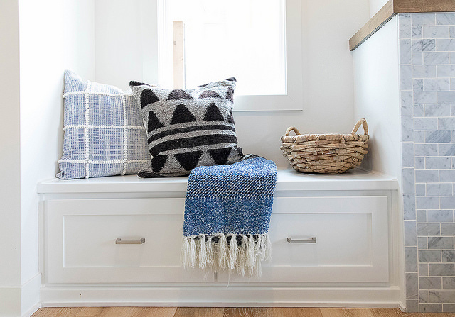 Stylish throw pillows and blanket on custom cabinetry.