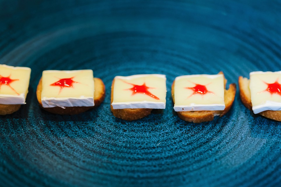 colourful red and white canapes on a black plate from private chef tom burney of hong kong personal chef