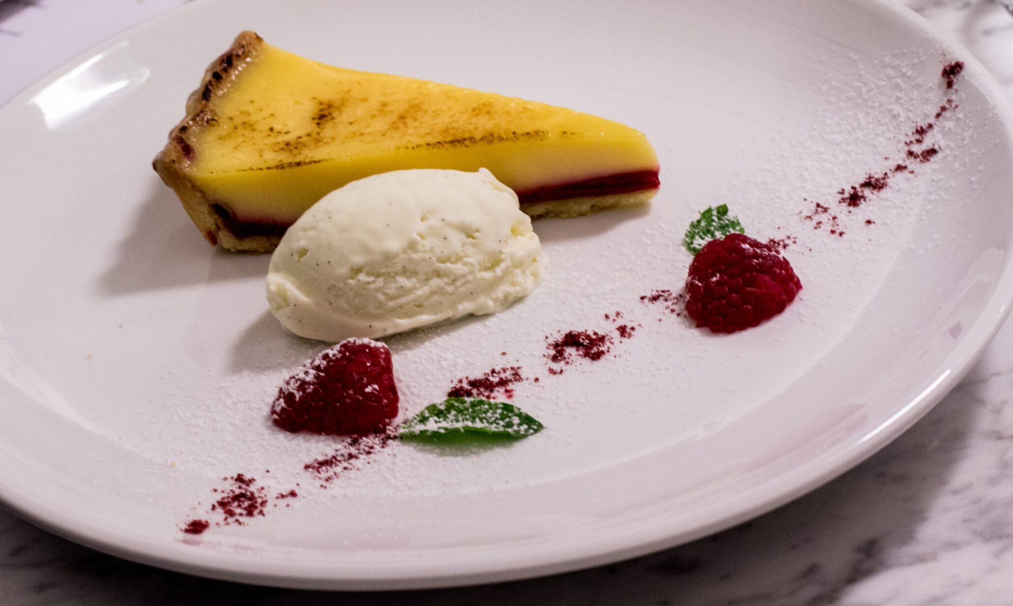 a plated lemon tart and raspberry dish for private dinner party