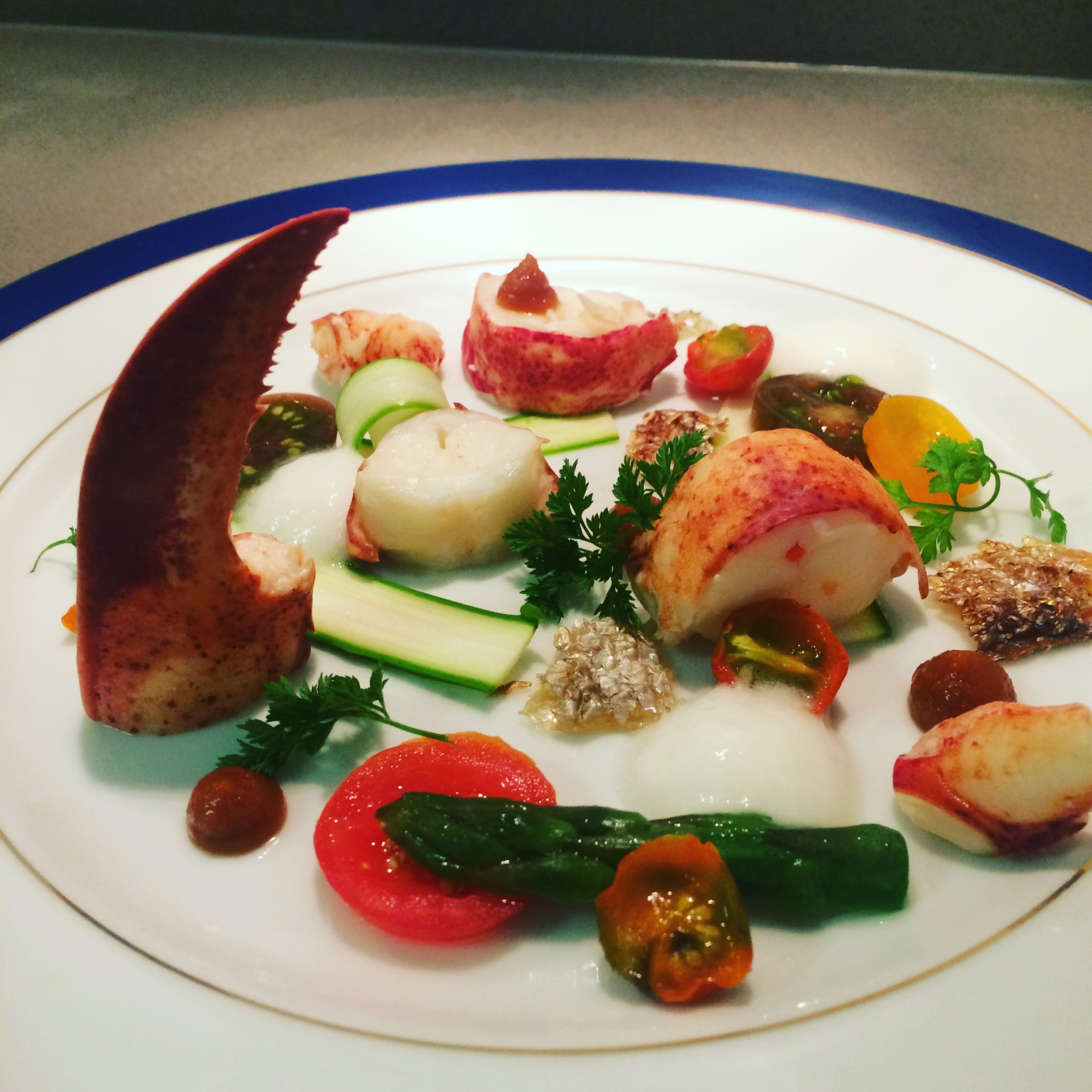 dinner party lobster salad on white plate with blue rim