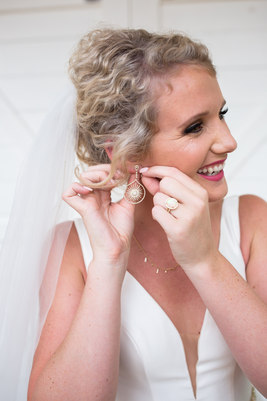 New Braunfels Texas bride putting on earrings