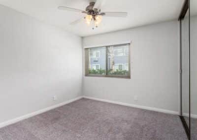 Open carpeted bedroom and ceiling fan