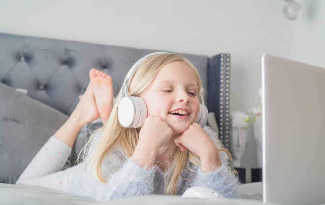 Child smiling while watching on her laptop wearing headphones