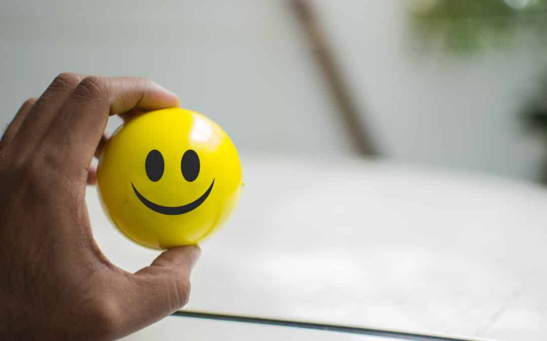 a hand holding a ball with a smiley print