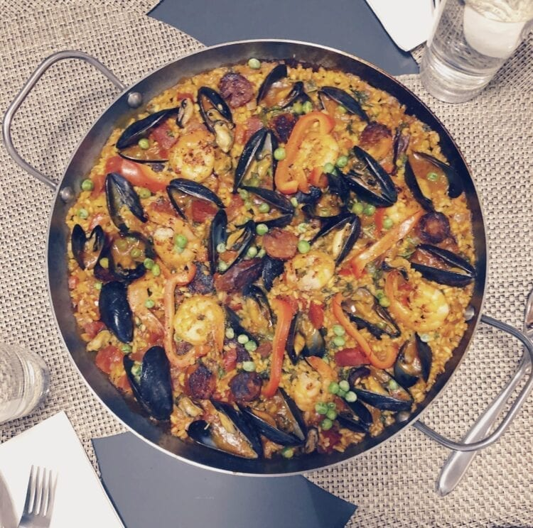 Delicious paella flavored with chorizo, muscles, clams, shrimp and saffron