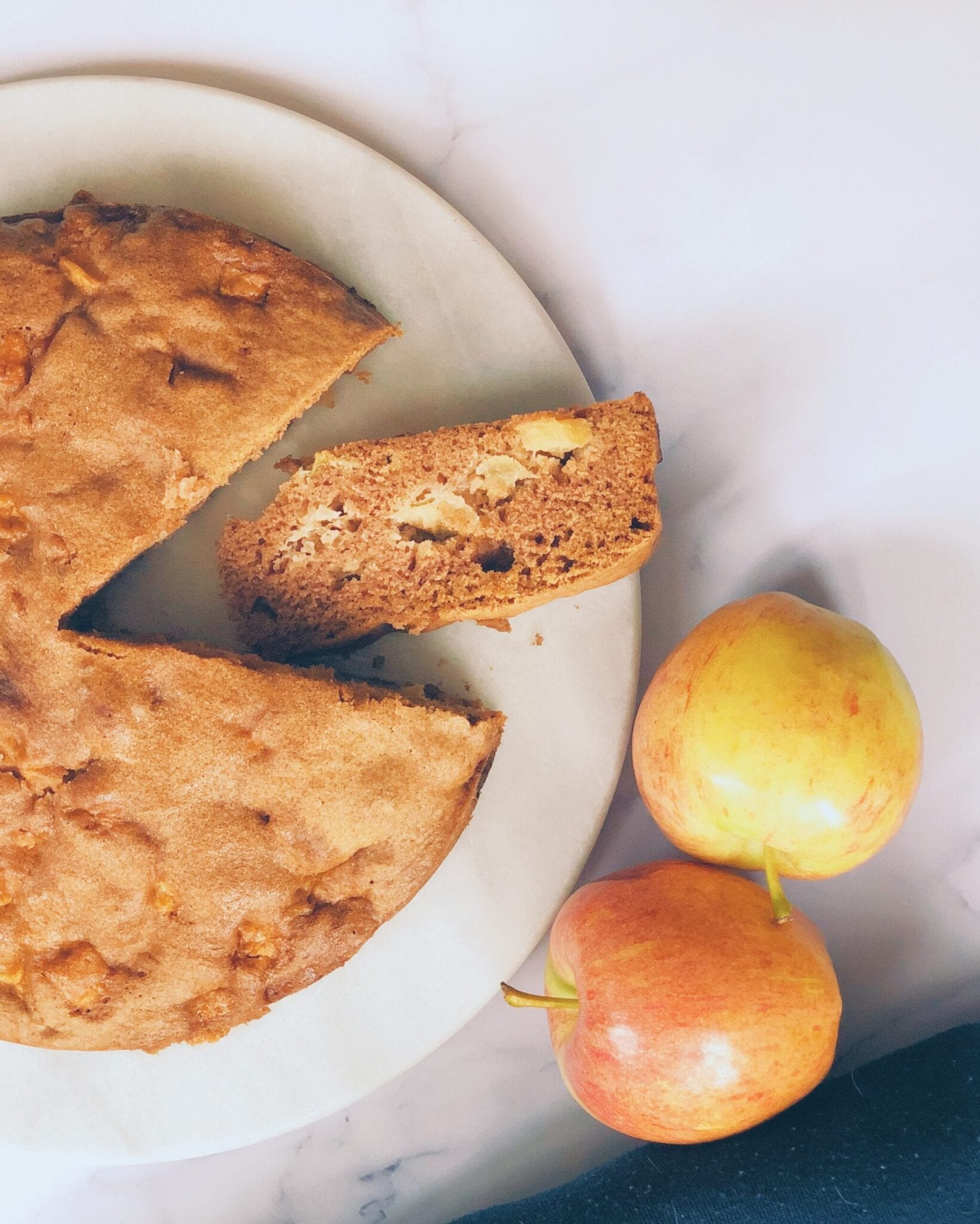 Slice of apple cake withe rest of cake and apples