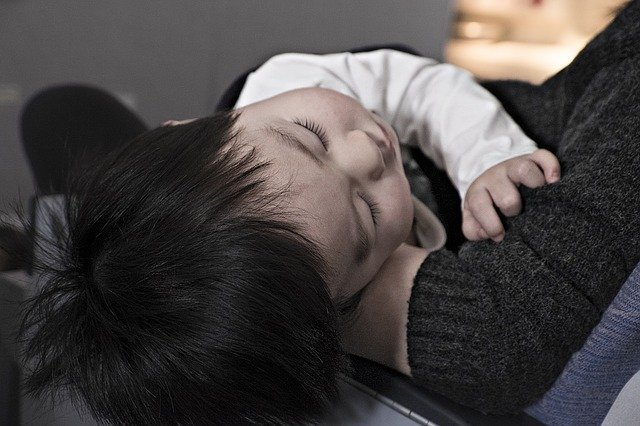 Autism And Sleep - A Toddler Sleeping In Its Parents Arms