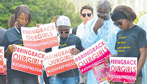 Three of the girls that escaped from the Boko Haram militants during the mass kidnapping in Chibok last April bow their heads in prayer before the #BringBackOurGirls press conference at the U.S. Capitol in Washington, D.C. Emmanuel Ogebe (second from right) joins them. (PHOTO BY FREDDIE ALLEN/NNPA NEWS WIRE)
