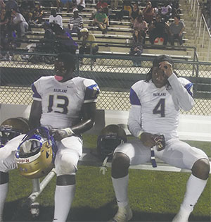Mainland High School teammates wait on the sideline during a game this season.