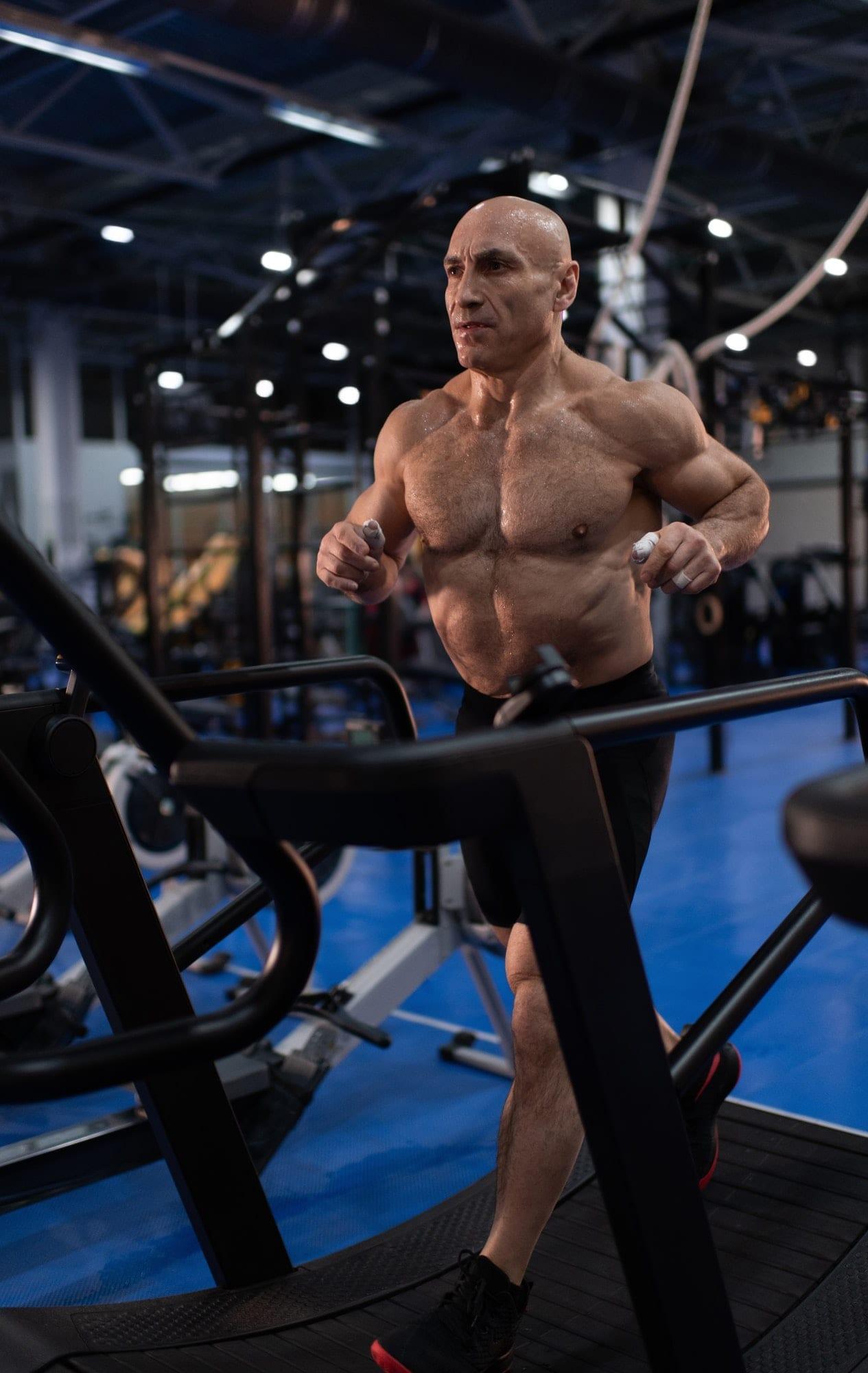 Sweaty old man running on modern treadmill