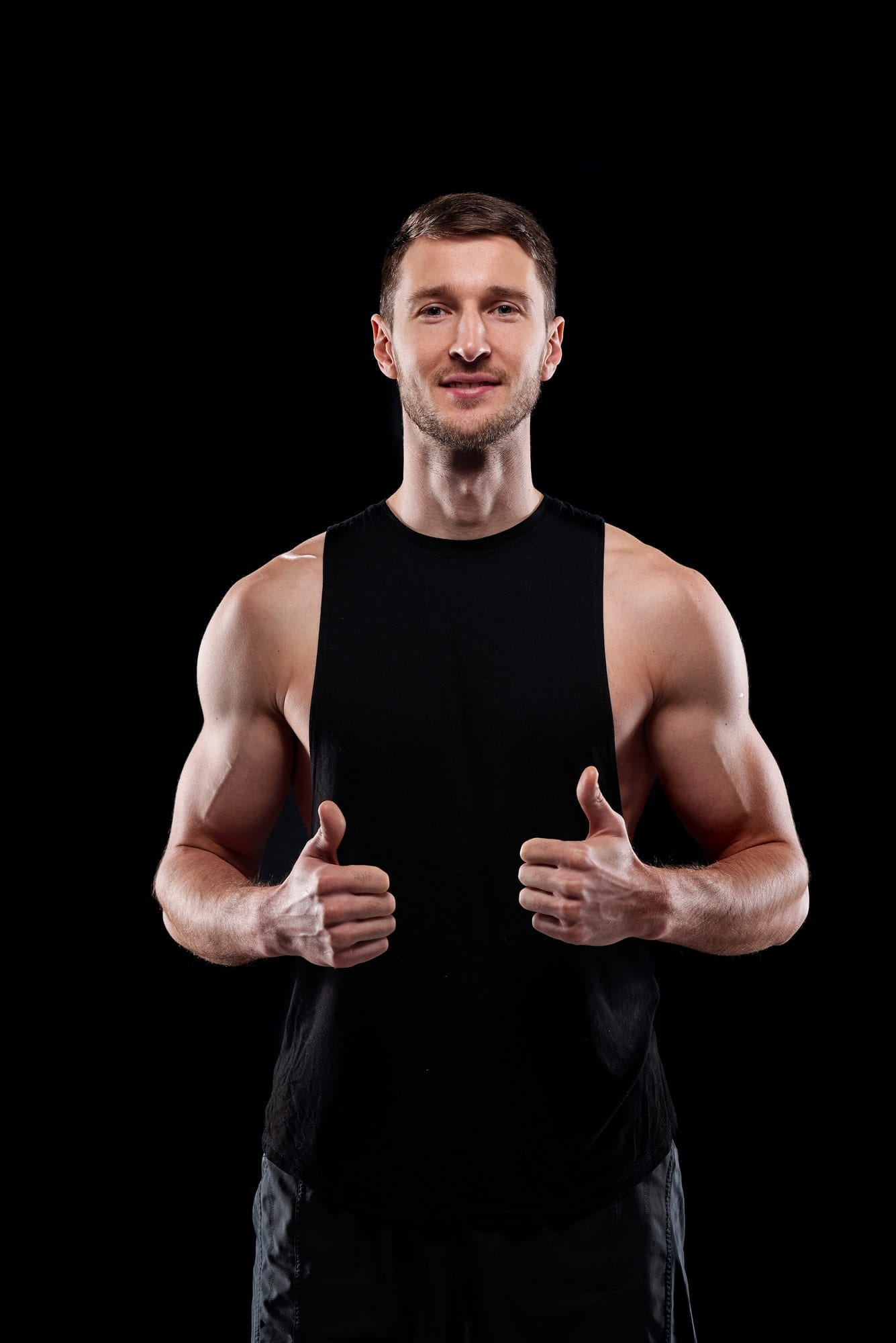 Young successful muscular sportsman showing thumbs up in front of camera