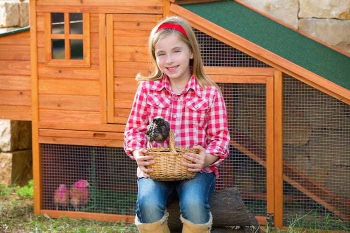 girl by chicken coop