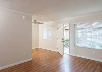 Empty living room with open door and ceiling fan