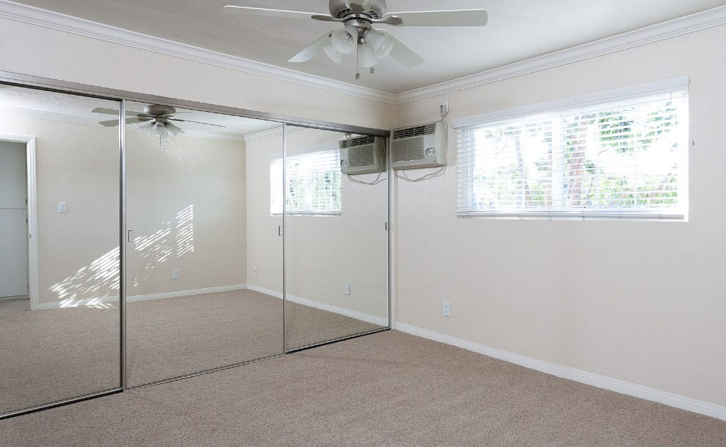 Empty bedroom with windows and ceiling fan