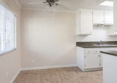 Empty dining room and kitchen with white cabinetry