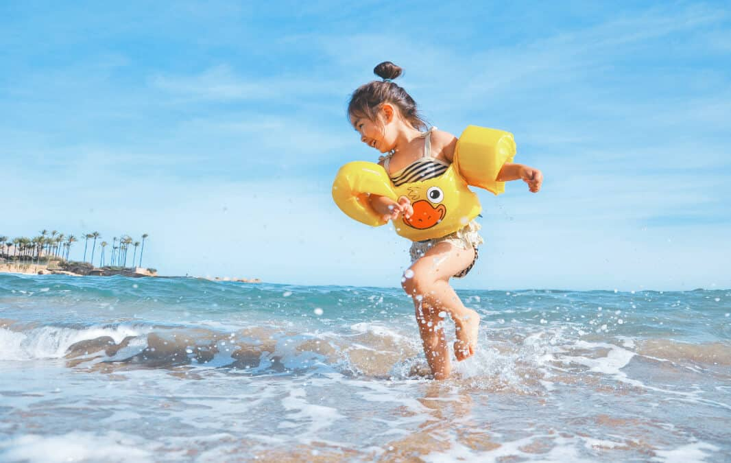 A child wearing floaters splashing in the beach
