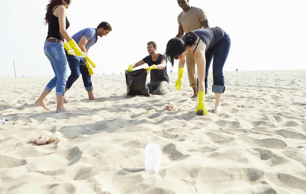 a group of people picking up trash on the beach all wearing yellow gloves