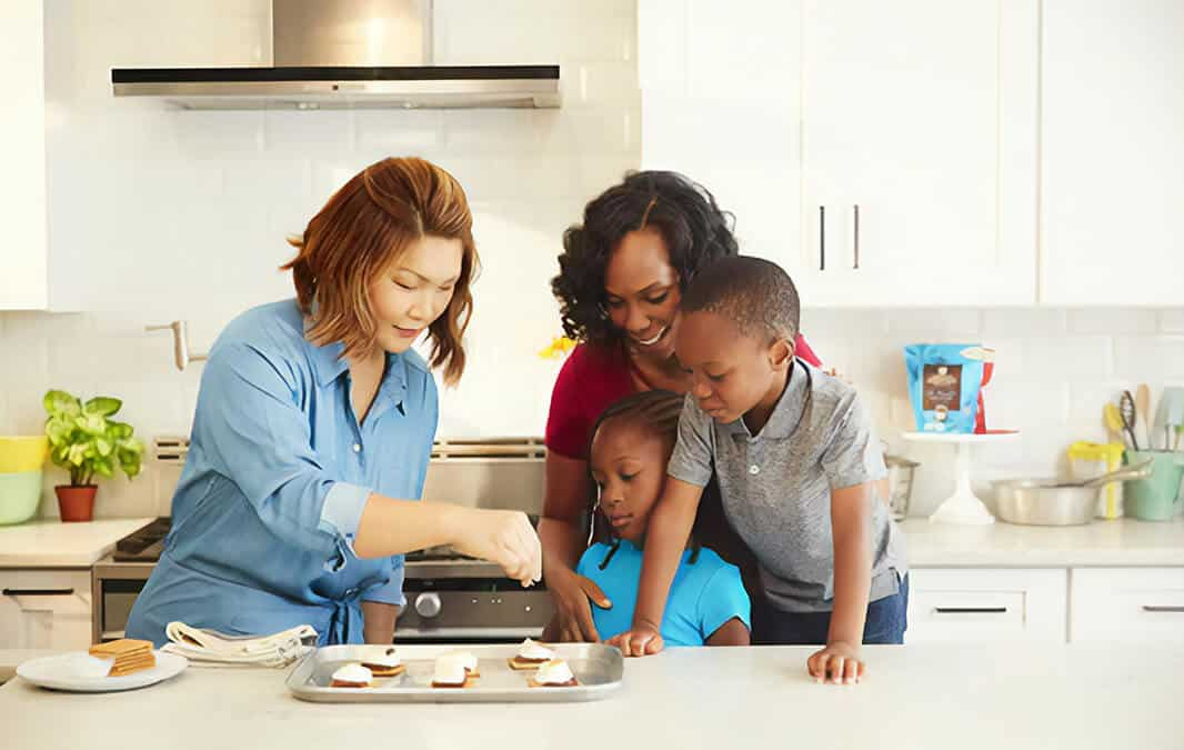 two women and kids making a treat