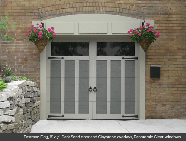 Eastman E-13 Dark Sand Garaga garage doors with Claystone overlays and Panoramic clear windows