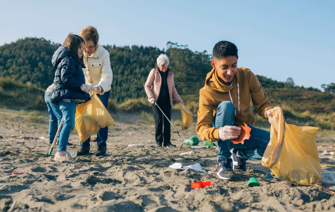 two children and two elderly women cleaning up the trash on the beach