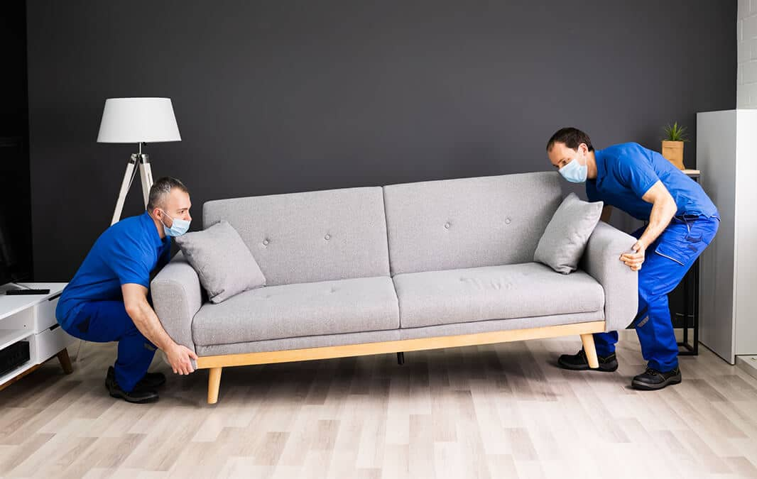 Two men in masks moving couch