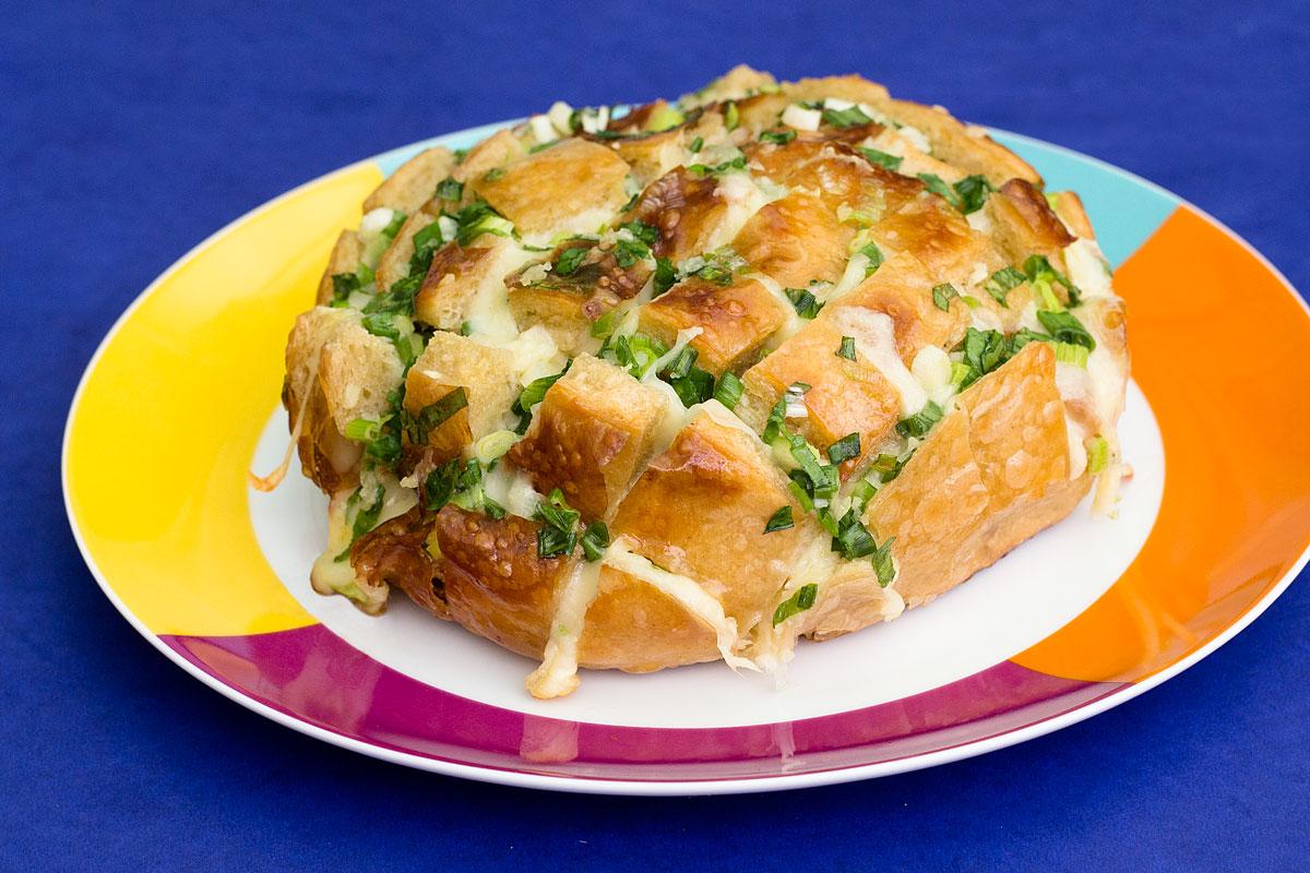 Foto do pão italiano com queijo recheado com manteiga, alho e cebolinha.