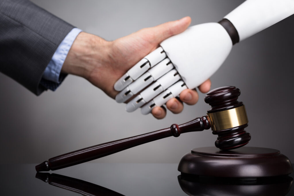 Human shaking hands with robot over judicial gavel