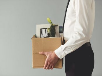 Picture o man leaving office with box of personal possessions