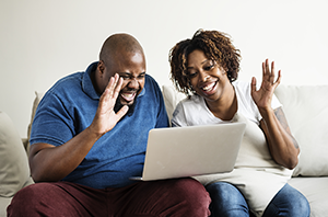 African American couple using a computer to talk with others.