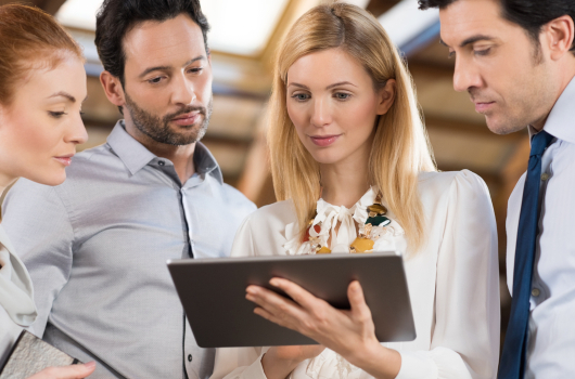 Maberry Consulting: Business people standing in the office and looking at a digital tablet. Businesswoman holding tablet