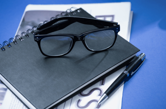 Notebook with glasses and pen