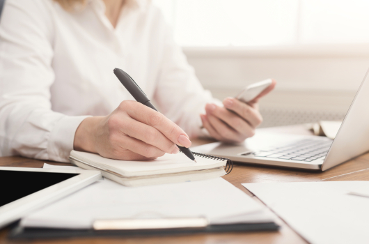 Close up of woman's hands holding smartphone and writing notes in notebook