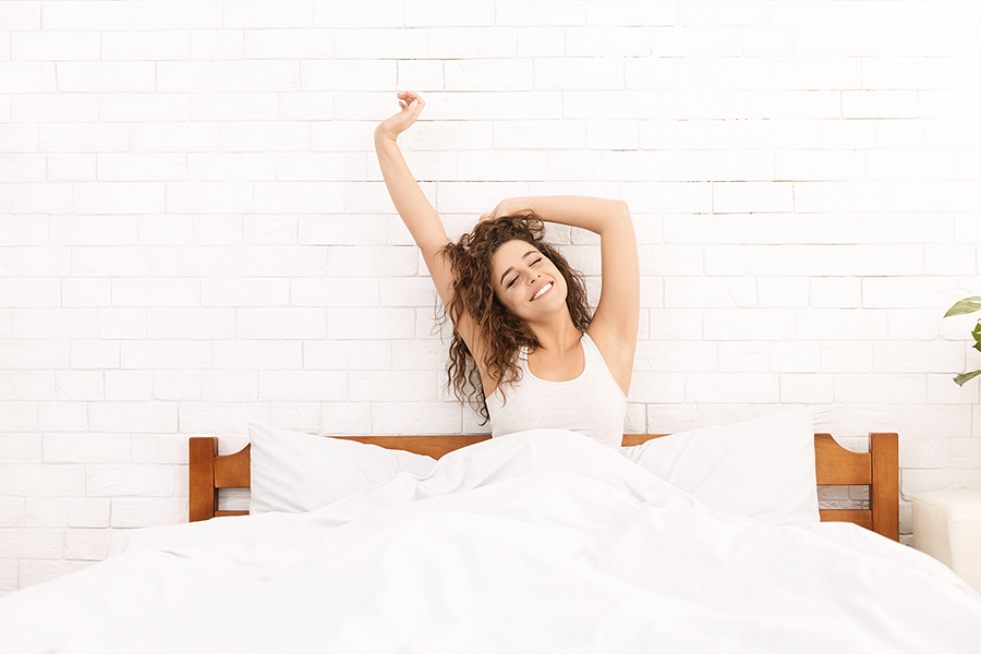 Woman sitting up in bed stretching her arms
