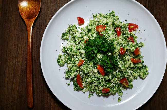 Plate of Cauliflower Tabbouleh Salad and tomatoes with a wooden spoon next to the plate