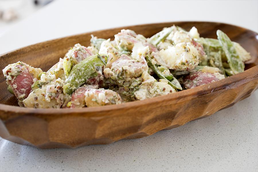 Long wooden bowl with Creamy Lemon Potato and Snap Pea Potato Salad