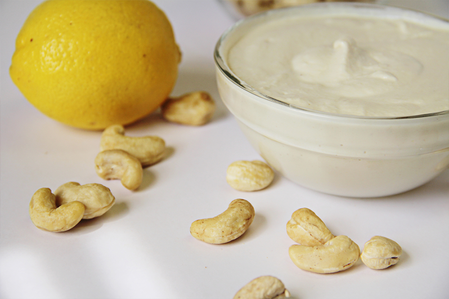 Sauce bowl of cashew cream sauce with scattered cashews arond the bowl and lemon