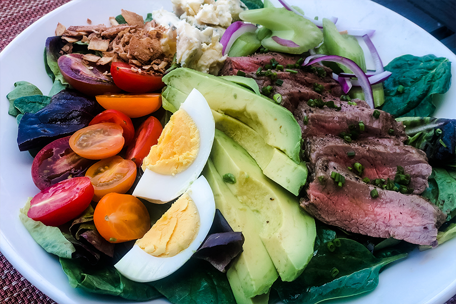 Cobb salad with tomatoes, hard boiled eggs, flank steak, avocado and other toppings