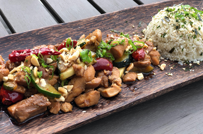 Kung Pao Chicken plated on a long wooden plate with a mound of rice