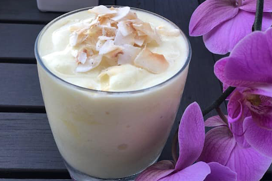 Pineapple-Toasted Coconut Smoothie in a glass next to purple orchids