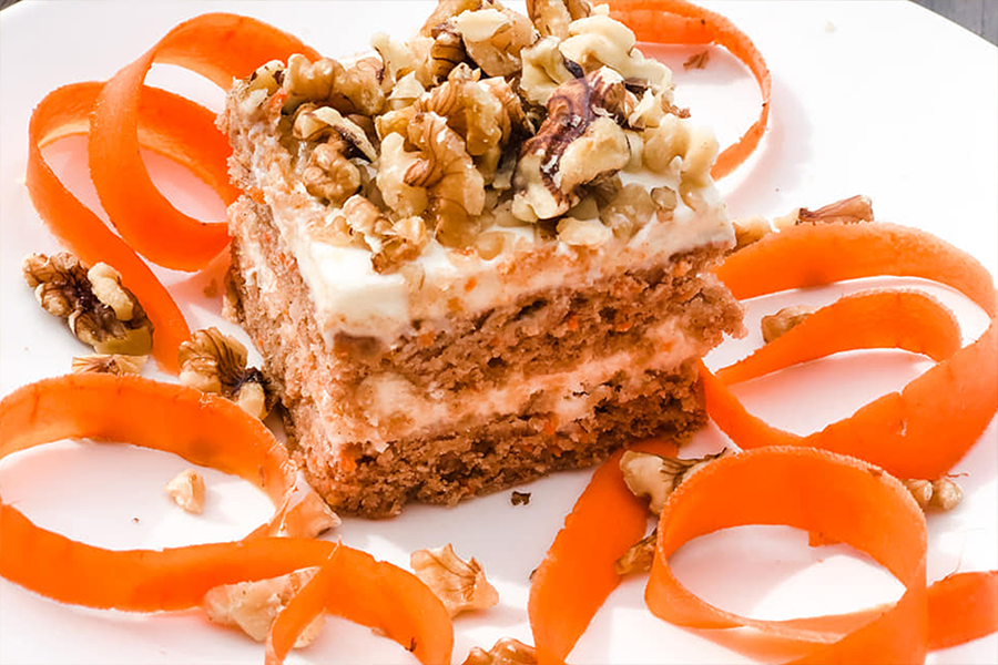 Square piece of Vegan Carrot Cake topped with almonds on a plate decorated with carrot ribbons