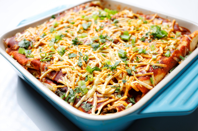 Baking dish with Vegan Ranchero Bean, Tempeh, Kale, and Sweet Potato Enchiladas