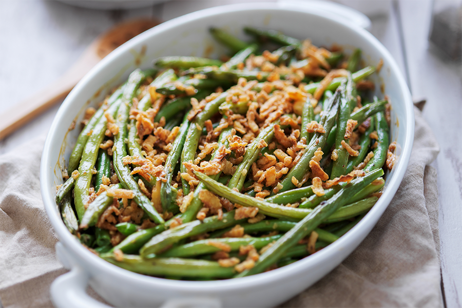 Baking dish of green bean casserole topped with crispy onions