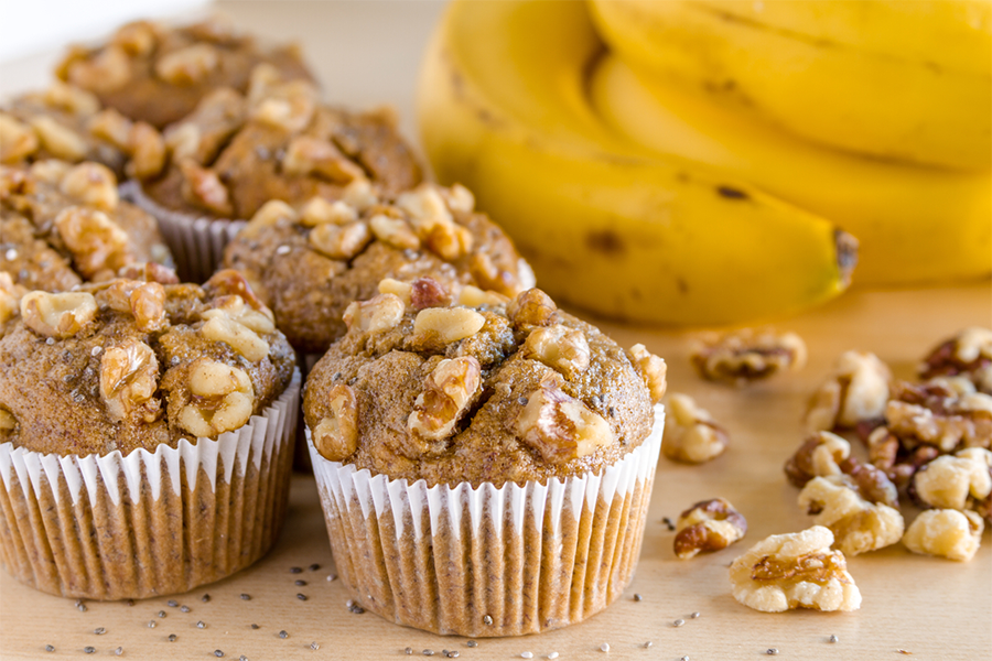 A half dozen banana walnut muffins next to a bunch of bananas and scattered walnuts