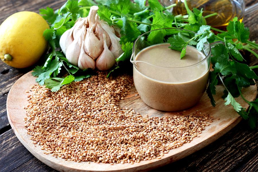 Plate of sesame seeds, a head of garlic, and sauce bowl of tahini sauce
