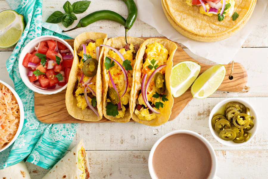 3 Veggie Smoked Gouda Breakfast Tacos on a cutting board with a bowl of salsa and limes.