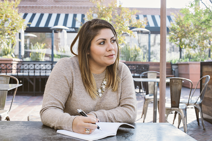 A young latina woman sits at a cafe with a journal, thinking about her goals for the coming year