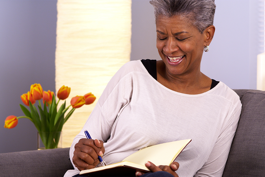 Senior black woman writing in journal on the couch