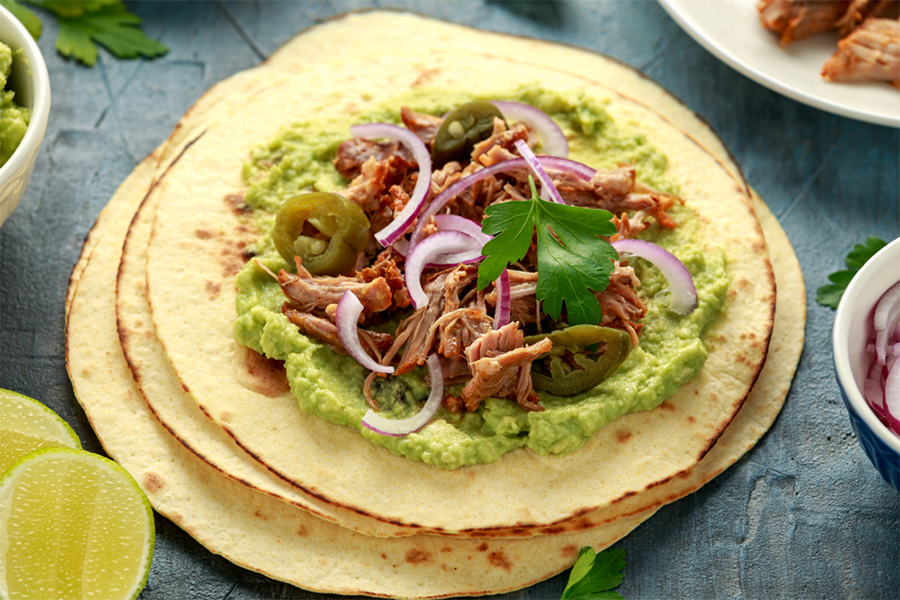 Tortillas with guacamole, jackfruit carnitas and onion on top