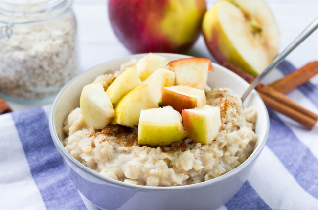 Bowl of oatmeal with chunks of apples on top