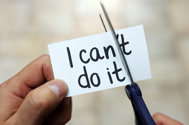 "Hand holding a piece of paper that says ""I can't do it"" with scissors cutting off the ""'t"" so it say ""I can do it"""